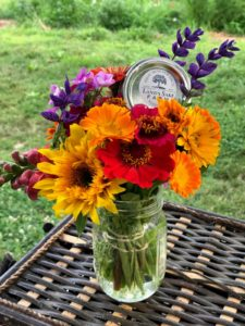 a variety of flowers arranged in mason jar